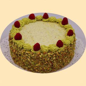 Pisztácia krém torta oldala pisztáciába forgatva, teteje pisztáciakrémmel és málnaszemekkel díszítve