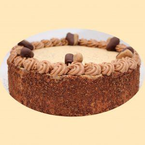 Gesztenye torta csokoládépanírral az oldalán tetején félig csokiba mártott gesztenye szívekkel díszítve.
