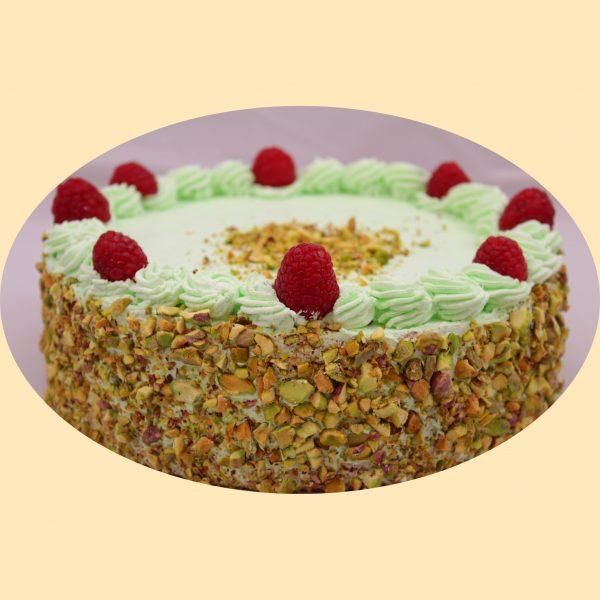 Pisztácia krém torta oldala pisztáciába forgatva, teteje pisztáciakrémmel és málnaszemekkel díszítve .