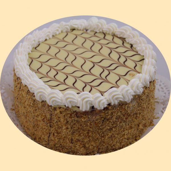 Eszterházy torta diópanírral teteje csokoládéval díszített fondannal, és tejszínhabbal díszítve