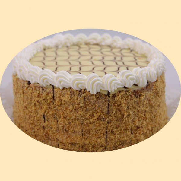 Eszterházy torta diópanírral teteje csokoládéval díszített fondannal, és tejszínhabbal díszítve.