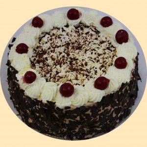 Feketeerdő torta tetején tejszínhabbal, oldalán csokoládépanírral, meggyekkel és csokoládéreszelékkel díszítve.