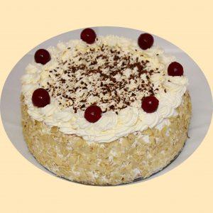 Feketeerdő torta tetején tejszínhabbal, oldalán szeletelt mogyorópanírral, meggyekkel és csokoládéreszelékkel díszítve.