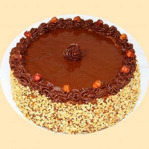 Mogyorókrémes torta oldala mogyorópanírral, teteje csokoládéval áthúzva és mogyorókrémmel illetve egészmogyoróval díszítve.