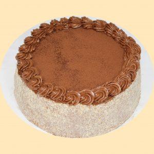 Doboslapok között dobos krémmel töltött torta kakaóporral megszórva a tetején.
