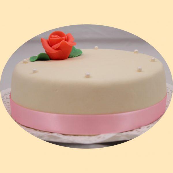 Marcipán bevonatos kerek torta rózsaszín szaténszallaggal és egy darab piros marcipánrózsával díszítve.