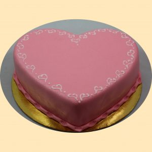 Szív alakú rózsaszín marcipánbevonatos torta széle fehér szívecskékkel díszítve.