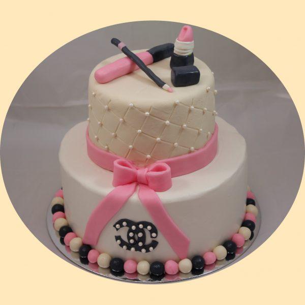 Kétszintes torta felül steppelt oldaldíszítéssel marcipán szájfénnyel, szemceruzável, és rúzzsal díszítve, rózsaszín fondant szallaggal átkötve.
