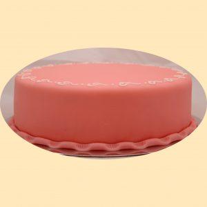 Rózsaszín marcipán bevonatos kerek torta szélén szívecske díszítéssel.