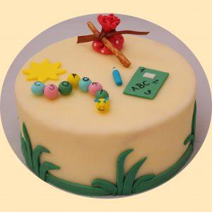 Bevonatos torta marcipán figurákkal, napocska tarisznya ceruza, füzet kukaccal díszítve.