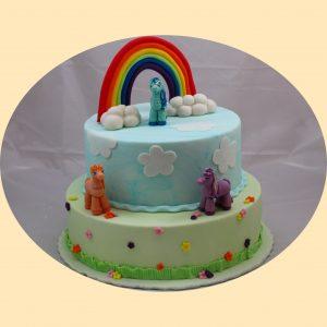 Emeletes kétszintes torta, alul zöld felül kék bevonattal, szivárvánnyal és három pónilovas marcipán figurával díszítve.