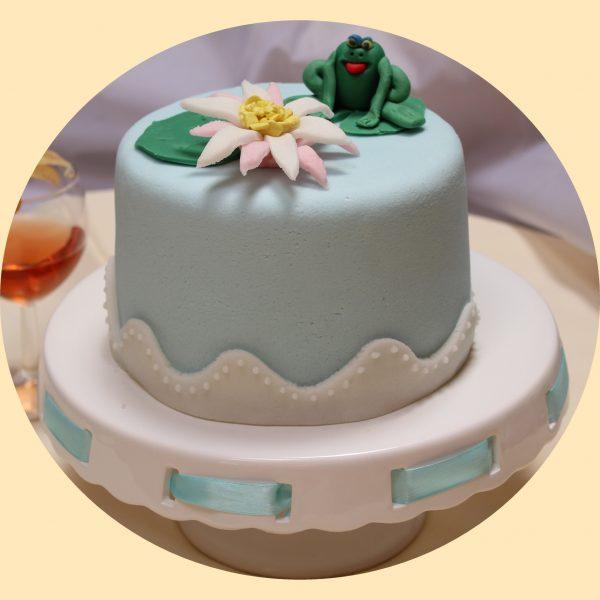 Halványkék bevonatú torta tavirózsa és béka díszítéssel a tetején.