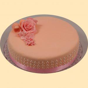 Barackvirág színű fondant bevonatos kerek torta rózsaszín szaténszallaggal és rózsaszín marcipán virágcsokorral díszítve, oldalán glazúr pöttyökkel.