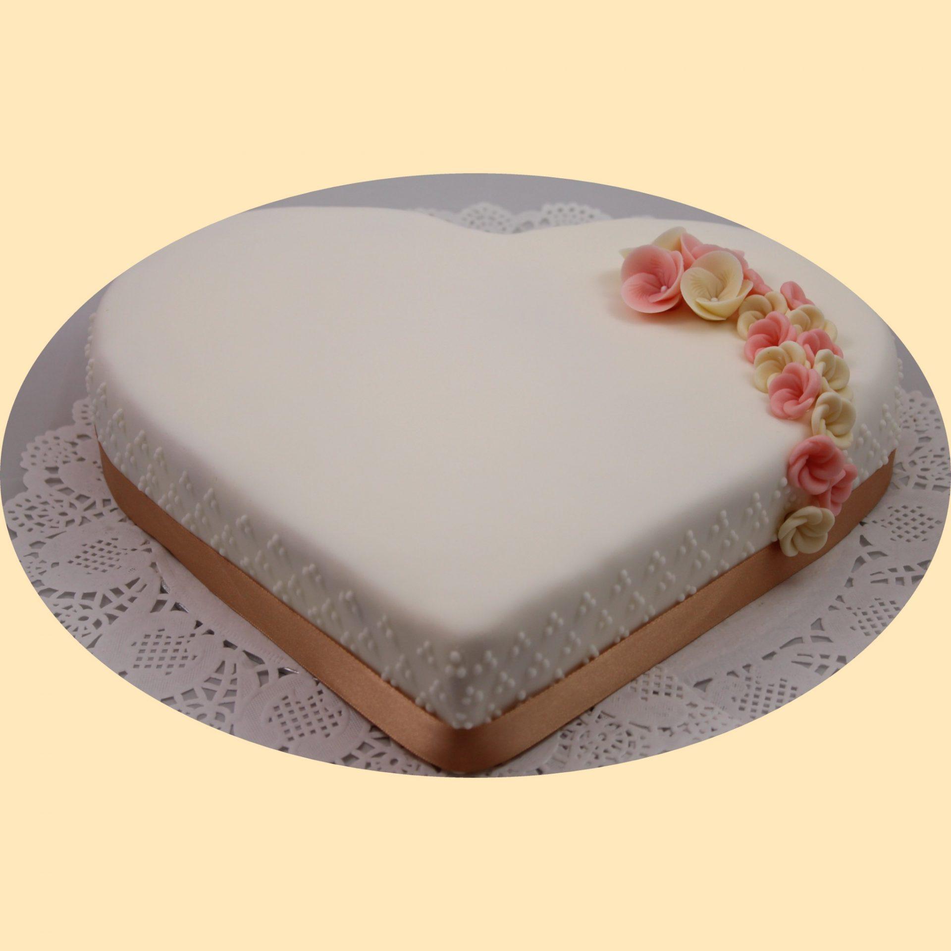 Fehér fondant bevonatos szív alakú formatorta, barna szaténszallaggal és fehér, rózsaszín apróvirággal díszítve.