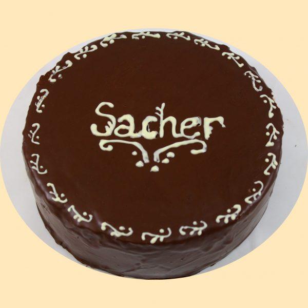 Teljes csokoládé bevonatos sacher torta, a torta széle apró fehér virágmotívummal díszítve.