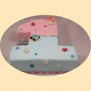 Szám formájú torta, kétszínű babakék, és babarózsaszín fondannal burkolva, kisautó és cumi marcipánfigurával díszítve.